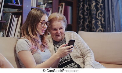 Young smiling granddaughter teaching a mobile phone to her grandmother