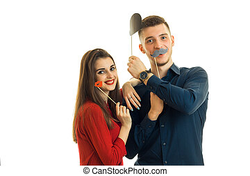young smiling guy with girl, hold near face paper props in the form of lips, moustache and hats for a photo