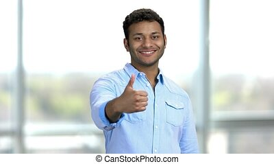 Young smiling hindu man showing thumb up. Indian guy in a blue shirt showing like and approve sign, standing indoors in a bright room.