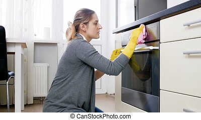 Young smiling housewife cleaning glass door of electric oven on kitchen