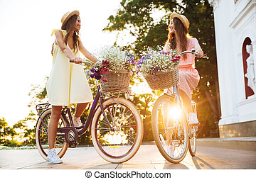 Young smiling ladies outdoors on bicycles. Looking aside.