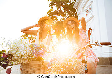 Young smiling ladies outdoors on bicycles. Looking camera.