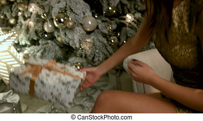 Young smiling lady opening Chistmas gift that she has found near the Xmas tree.