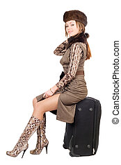 Young smiling lady sits on a suitcase