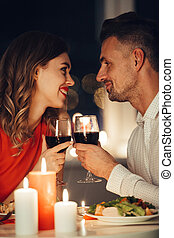 Young smiling lovers looking at each other and have romantic dinner with wine and food