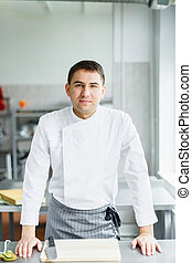 Young smiling male chef posing