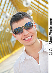 young smiling man in sunglasses on footbridge