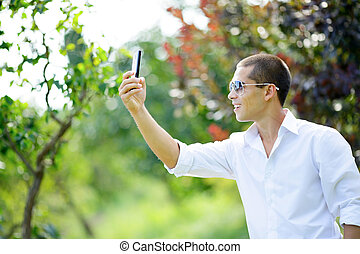 Young smiling man in sunglasses taking selfie