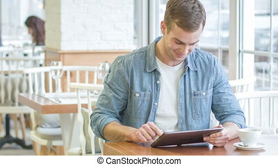 Young smiling man is busy with his digital tablet. - Man...
