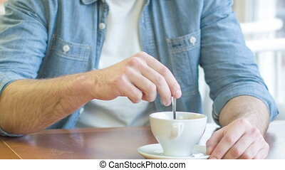 Young smiling man is mixing his coffee with sugar. - Coffee...