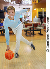 Young smiling man wearing blue sweater throws ball in bowling; shallow depth of field
