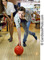 Young smiling man wearing ripped jeans throws ball in bowling; woman looks at man; shallow depth of field