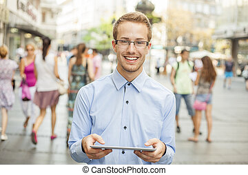 Young smiling man with tablet computer on street