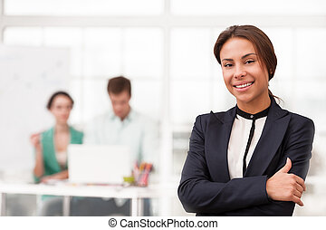 Young smiling mixed race businesswoman looking at camera