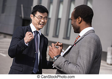 young smiling multiethnic businessmen in formalwear celebrating success, business team meeting