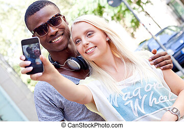 young smiling multiracial couple taking foto by smartphone ...