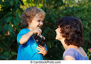 Young smiling photographer with a camera shoots her mother...