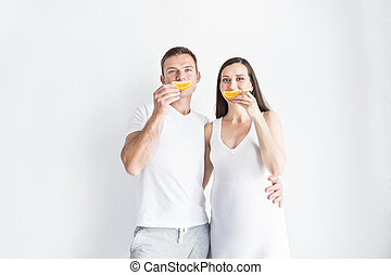 Young smiling pregnant woman and man with fruit