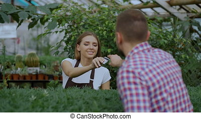 Young smiling seller florist working in garden center. Woman gives shopping bag to customer and making payment by credit card at store