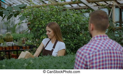Young smiling seller florist working in garden center. Woman...