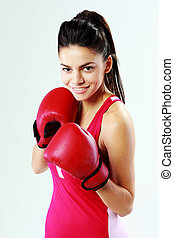 Young smiling sport woman boxing on gray background
