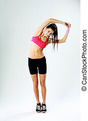 Young smiling sport woman stretching on gray background