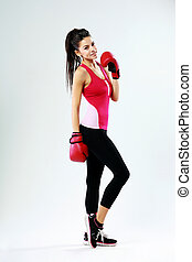 Young smiling sports woman standing with boxing gloves on gray background