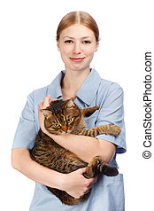 Young smiling veterinarian woman hugging adult scared tabby cat