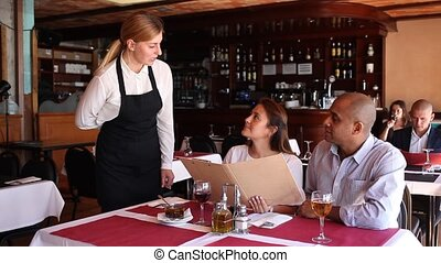 Polite young waitress taking order in pizza restaurant, helping positive couple in choosing meals from menu