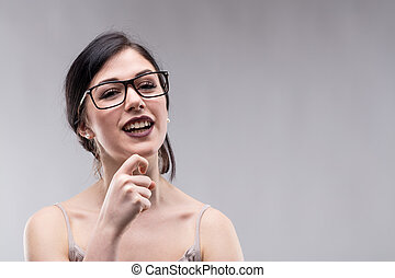 Young smiling woman against grey background