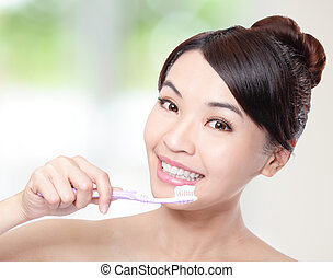 smiling woman cleaning teeth with toothbrush