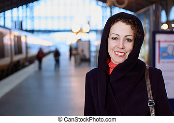 Young smiling woman close-up stands on the railway platform. The train on the left, shallow depth of focus.