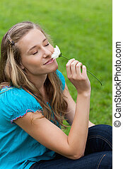 Young smiling woman closing her eyes while smelling a flower