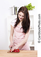young smiling woman cutting red paprika