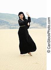 Young smiling woman dancing in desert