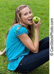 Young smiling woman eating a green apple while sitting down on the grass in a park