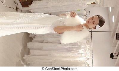 woman flaunting dressed in wedding gown in wedding salon - ...
