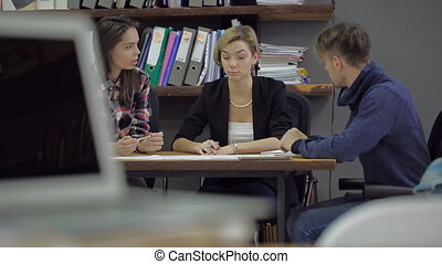 Young smiling woman gesticulating, telling something to the girl and the guy