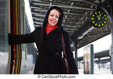 Young smiling woman going to enter a train.