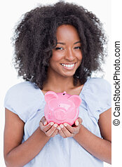 Young smiling woman holding a piggy bank