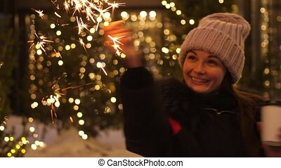 Young smiling woman holding burning sparkler and coffee in cold winter evening on street. Glowing blurred bokeh lights of Christmas