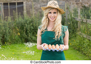 Young smiling woman holding carton of eggs