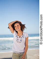 Young smiling woman holding her hair on the beach