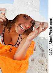 Young smiling woman holding her hat brim while lying down
