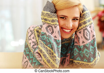 Young smiling woman in colorful sweater at home