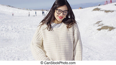 Young smiling woman in sweater on ski slope
