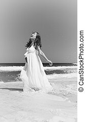 Young smiling woman in white dress standing in sea waves