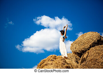 Young smiling woman in white dress standing on hay stack with raised hands