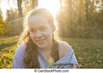 Young smiling woman in white hoodie sitting in the autumn park