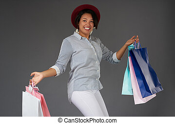 Young smiling woman jump with shop bags
